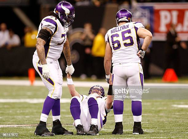 Brett Favre of the Minnesota Vikings is helped up by teammates Phil Loadholt and John Sullivan after he took a hard hit in the second half against...