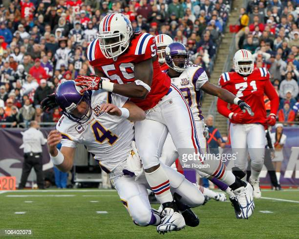 Brett Favre of the Minnesota Vikings is knocked down by Gary Guyton of the New England Patriots in the first half at Gillette Stadium on October 31,...