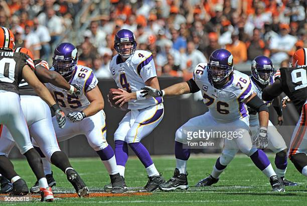 Brett Favre of the Minnesota Vikings looks for an open receiver while being protected by teammates John Sullivan and Steve Hutchinson during an NFL...
