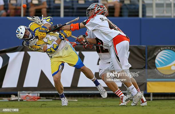 Brett Garber of the Florida Launch loses the ball guarded by Domenic Sebastiani of the Denver Outlaws during a game at FAU Stadium on April 26 2014...