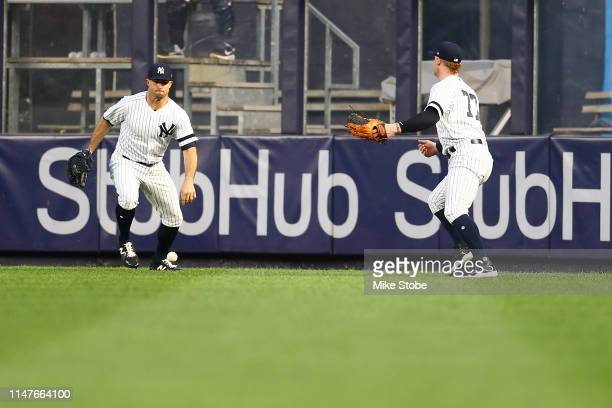 Brett Gardner and Clint Frazier of the New York Yankees watch the ball drop in between them off the bat from Jay Bruce of the Seattle Mariners in the...