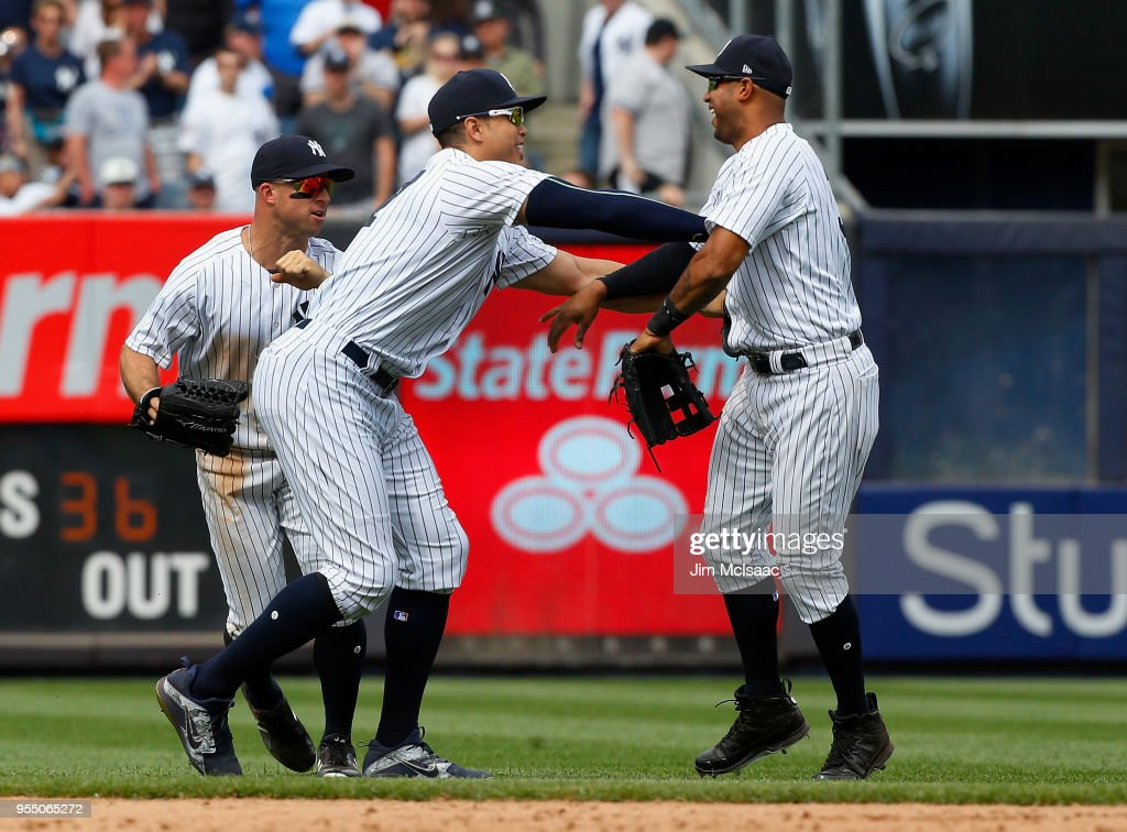 Brett Gardner #11, Giancarlo Stanton #27 and Aaron Hicks #31 of the New York Yankees celebrate after defeating the Cleveland Indians at Yankee Stadium on May 5, 2018 in the Bronx borough of New York City.