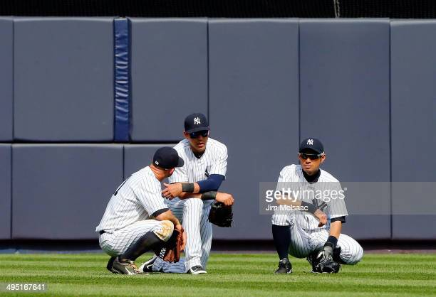 Brett Gardner Jacoby Ellsbury and Ichiro Suzuki of the New York Yankees look on during a pitching change in the ninth inning against the Minnesota...