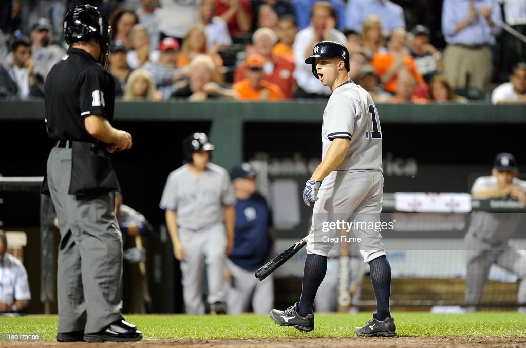 Brett Gardner #11 of the New York Yankees argues with home plate umpire Ed Hickox after being called out on strikes in the eighth inning against the Baltimore Orioles at Oriole Park at Camden Yards on September 9, 2013 in Baltimore, Maryland.
