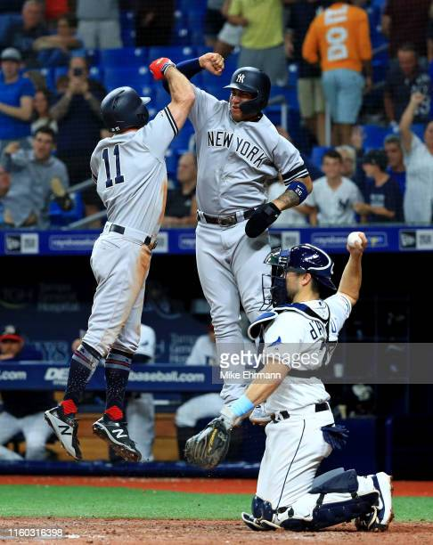 Brett Gardner of the New York Yankees celebrates a 3 run home run with Gleyber Torres in the 11th inning during a game against the Tampa Bay Rays at...