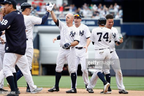 Brett Gardner of the New York Yankees celebrates with teammates after driving in the winning run in the ninth inning of a game against the Tampa Bay...