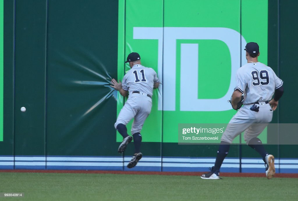 Brett Gardner #11 of the New York Yankees crashes into the outfield wall in pursuit of a double hit by Justin Smoak #14 of the Toronto Blue Jays as Aaron Judge #99 watches the play in the sixth inning during MLB game action at Rogers Centre on July 7, 2018 in Toronto, Canada.