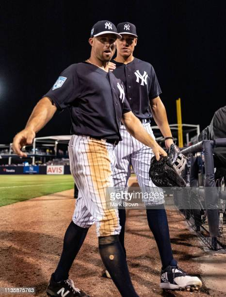 Brett Gardner of the New York Yankees heads to the dugout with Aaron Judge during the spring training game against the Philadelphia Phillies at...