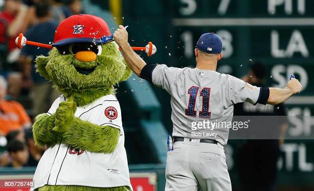 Brett Gardner of the New York Yankees hits Houston Astros mascot Orbit with a bag of sunflower seeds at Minute Maid Park on July 2 2017 in Houston...
