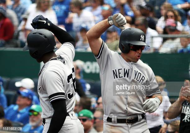 Brett Gardner of the New York Yankees is congratulated by Cameron Maybin after scoring during the 5th inning of the game at Kauffman Stadium on May...