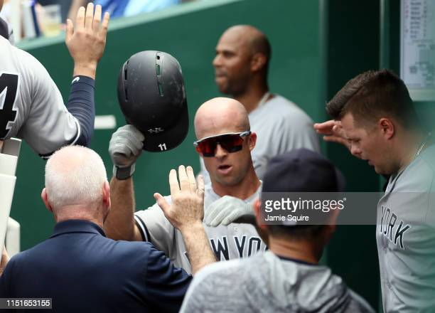 Brett Gardner of the New York Yankees is congratulated by teammates in the dugout after scoring during the 5th inning of the game against the Kansas...