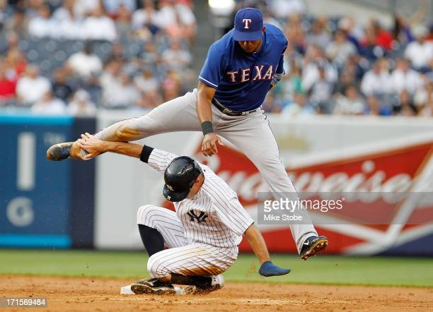 Brett Gardner of the New York Yankees is forced out at second as Elvis Andrus of the Texas Rangers completes the double play at Yankee Stadium on...