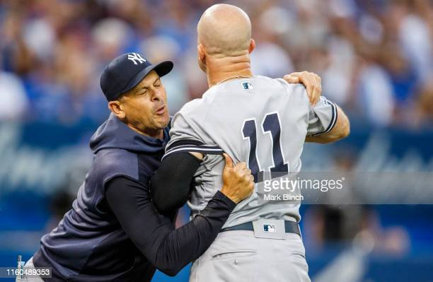 Brett Gardner of the New York Yankees is held back by manager Aaron Boone as he argues with umpires while playing the Toronto Blue Jays in the fourth...