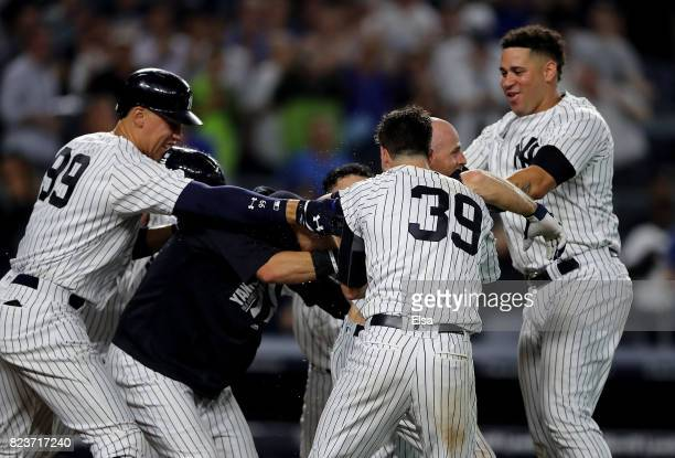 Brett Gardner of the New York Yankees is mobbed by teammates Aaron JudgeTyler Wade and Gary Sanchez after Gardner hit a walk off home run in the 11th...