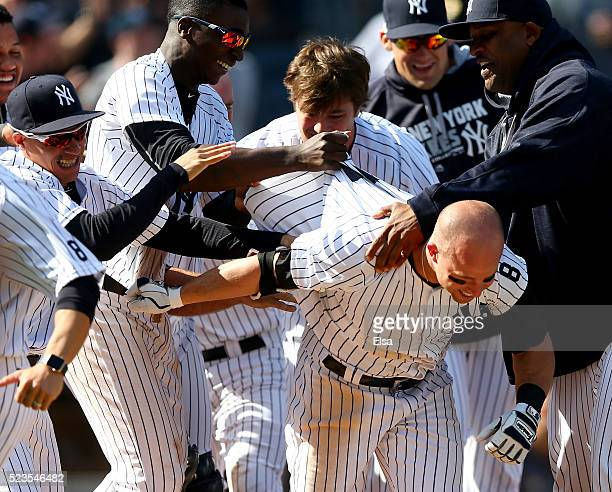 Brett Gardner of the New York Yankees is mobbed by teammates after he hit a walkoff home run to win the game against the Tampa Bay Rays at Yankee...