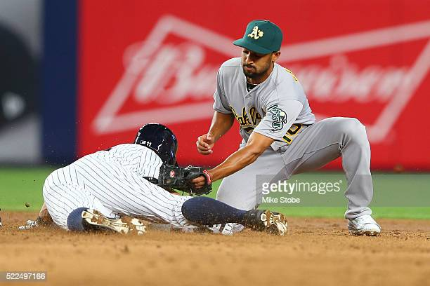 Brett Gardner of the New York Yankees slides in ahead of the tag of Marcus Semien of the Oakland Athletics for a third inning double at Yankee...