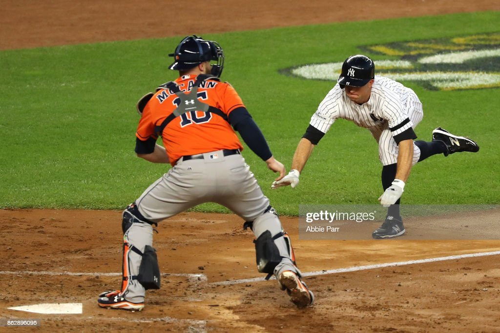 Brett Gardner #11 of the New York Yankees slides in safely at home plate to score on a double by Aaron Judge #99 against Brian McCann #16 of the Houston Astros during the third inning in Game Five of the American League Championship Series at Yankee Stadium on October 18, 2017 in the Bronx borough of New York City.