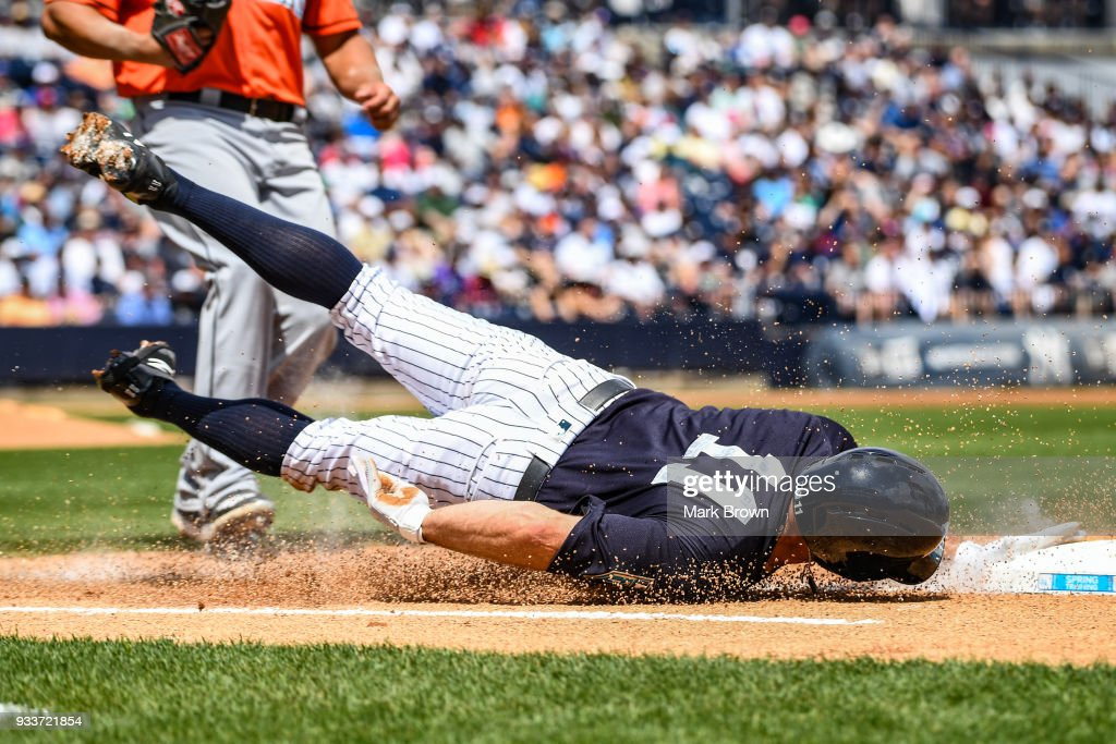 Brett Gardner #11 of the New York Yankees slides into first base in the first inning during the spring training game between the New York Yankees and the Miami Marlins at George M. Steinbrenner Field on March 18, 2018 in Tampa, Florida.