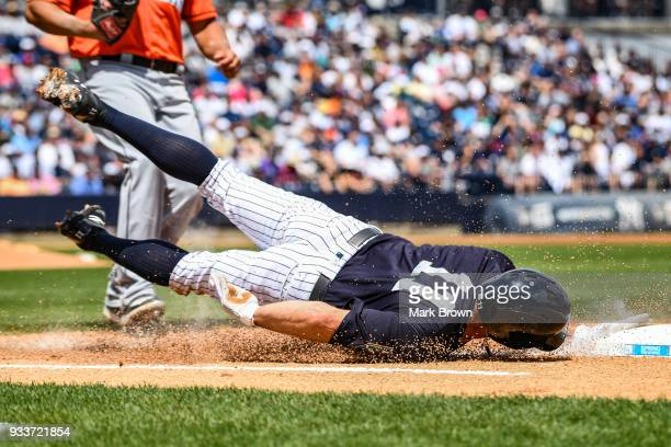 Brett Gardner of the New York Yankees slides into first base in the first inning during the spring training game between the New York Yankees and the...