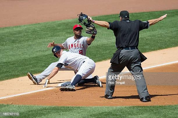Brett Gardner of the New York Yankees slides into third base after home plate umpire gestures safe during the game against the Los Angeles Angels at...