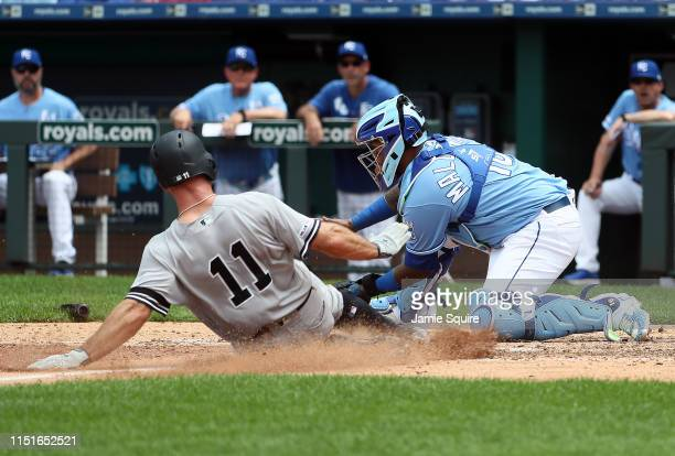Brett Gardner of the New York Yankees slides safely into home plate to score as Martin Maldonado of the Kansas City Royals is late applying the tag...