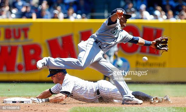Brett Gardner of the New York Yankees steals second base in the first inning ahead outfield the throw to Ketel Marte of the Seattle Mariners at...