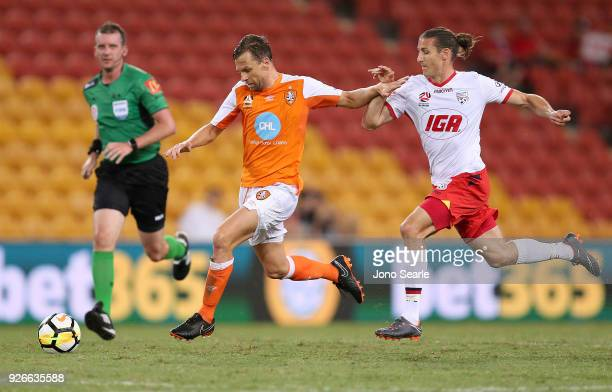 Brett Holman of the Brisbane Roar gets past Michael Marrone of Adelaide United during the round 22 ALeague match between the Brisbane Roar and...