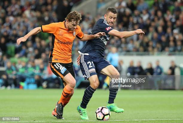Brett Holman of the Roar and Carl Valeri of the Victory compete for the ball during the ALeague Semi Final match between Melbourne Victory and the...