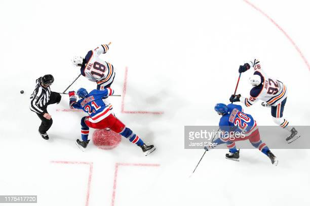 Brett Howden and Chris Kreider of the New York Rangers battle for the puck against James Neal and Tomas Jurco of the Edmonton Oilers at Madison...