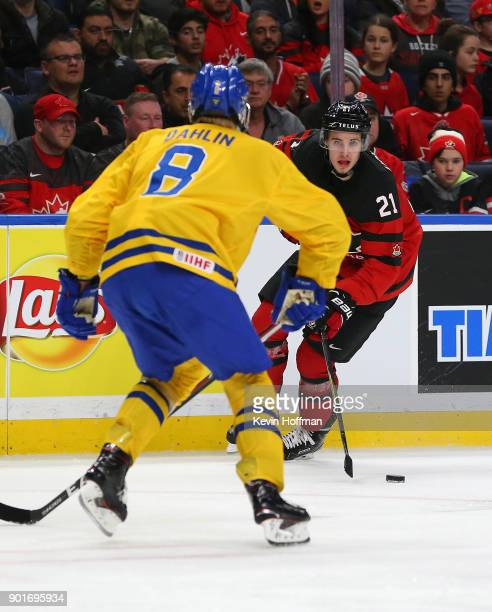 Brett Howden of Canada skates up ice with the puck as Rasmus Dahlin of Sweden defends during the Gold medal game of the IIHF World Junior...