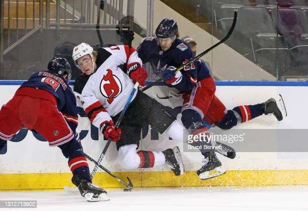 Brett Howden of the New York Rangers checks Tyce Thompson of the New Jersey Devils during the first period at Madison Square Garden on April 15, 2021...
