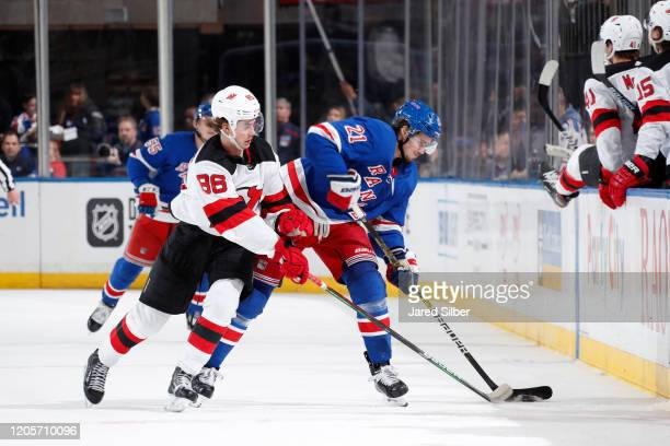Brett Howden of the New York Rangers skates with the puck against Jack Hughes of the New Jersey Devils at Madison Square Garden on March 7, 2020 in...