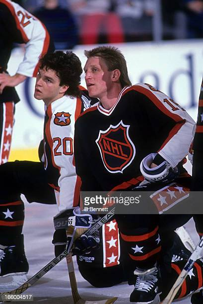 Brett Hull of the Campbell Conference and the St. Louis Blues kneels next to Luc Robitaille of the Los Angeles Kings before the 1990 41st NHL...