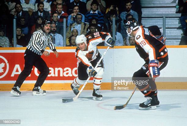 Brett Hull of the Campbell Conference and the St. Louis Blues looks to pass against Larry Robinson of the Wales Conference and the Montreal Canadiens...