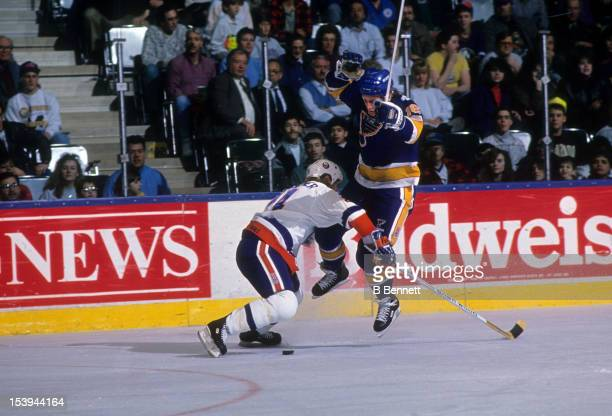 Brett Hull of the St. Louis Blues tries to avoid the check from Ken Baumgartner of the New York Islanders during an NHL game circa 1990 at the Nassau...