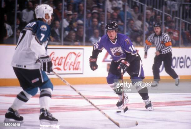 Brett Hull of the Western Conference and St Louis Blues skates with the puck as he is defended by Paul Coffey of the Eastern Conference and...