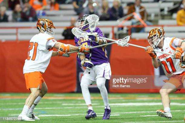 Brett Kennedy and Nick Mellen of the Syracuse Orange check Jakob Patterson of the Albany Great Danes to create a loose ball during the second half at...