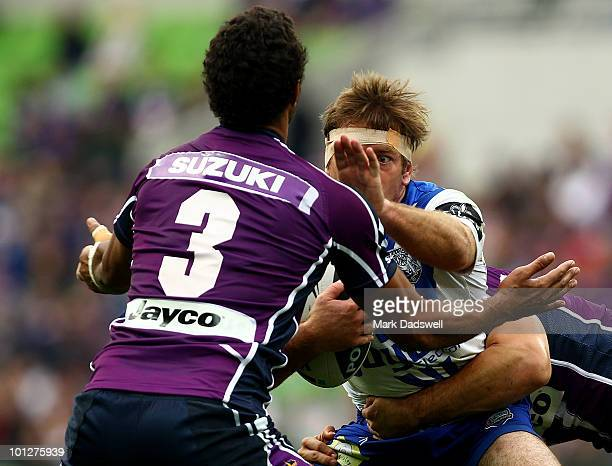 Brett Kimmorley of the Bulldogs attempts to push off Dane Nielsen of the Storm during the round 12 NRL match between the Melbourne Storm and the...