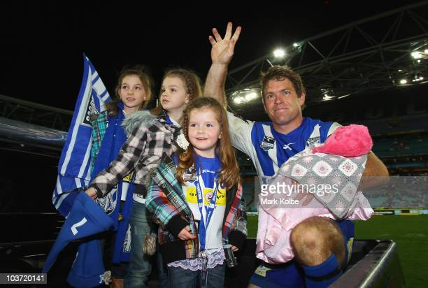 Brett Kimmorley of the Bulldogs waves to the crowd as he is joined by his four daughters Maddie, Mia, Ava and Ivy on his lap of honour after his...