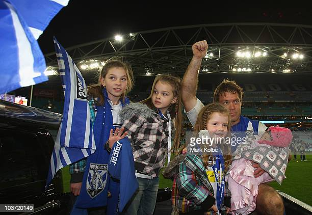 Brett Kimmorley of the Bulldogs waves to the crowd as he is joined by his four daughters Maddie Mia Ava and Ivy on his lap of honour after his final...