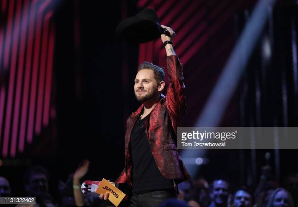 Brett Kissel tips his hat as he holds his award after winning the Country Album of the Year during the 2019 Juno Awards at Budweiser Gardens on March...