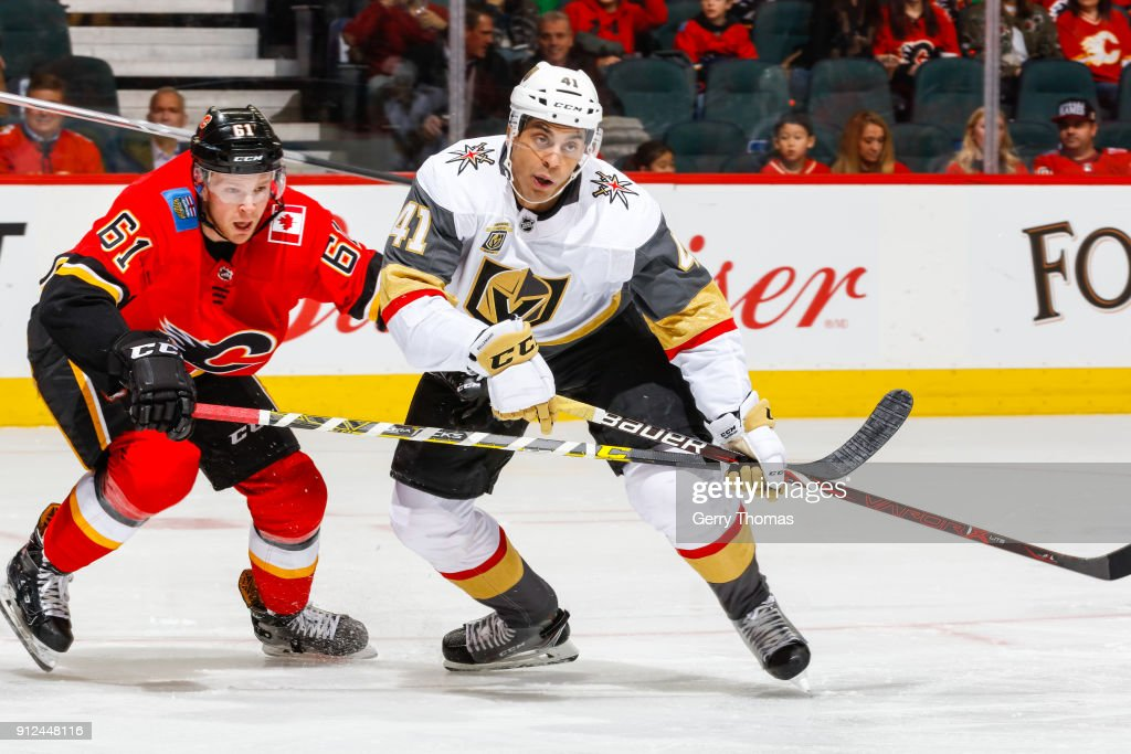Brett Kulak #61 of the Calgary Flames and Pierre-Edouard Bellemare #41 of the Vegas Golden Knights battle for position in an NHL game on January 30, 2018 at the Scotiabank Saddledome in Calgary, Alberta, Canada.