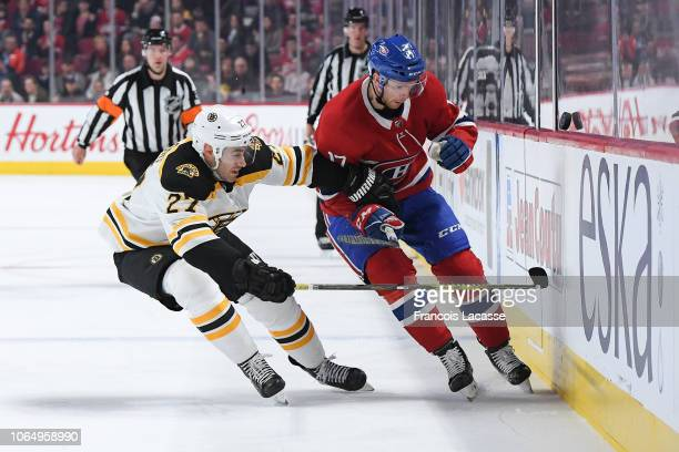 Brett Kulak of the Montreal Canadiens skates for the puck against John Moore of the Boston Bruins in the NHL game at the Bell Centre on November 24...