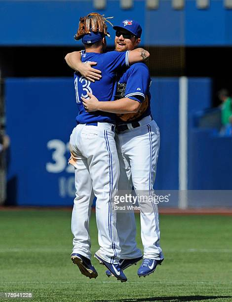 Brett Lawrie and Adam Lind of the Toronto Blue Jays celebrate the teams win over the Oakland Athletics during MLB game action August 10 2013 at...