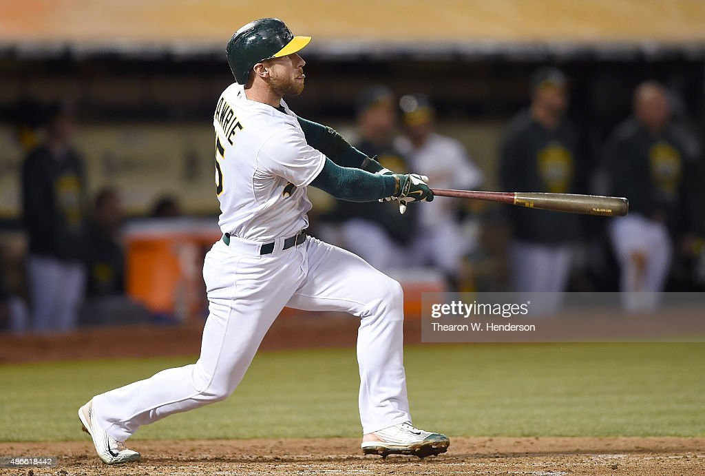 Brett Lawrie #15 of the Oakland Athletics hits an RBI double scoring Mark Canha #20 against the Seattle Mariners in the bottom of the secong inning at O.co Coliseum on September 4, 2015 in Oakland, California.