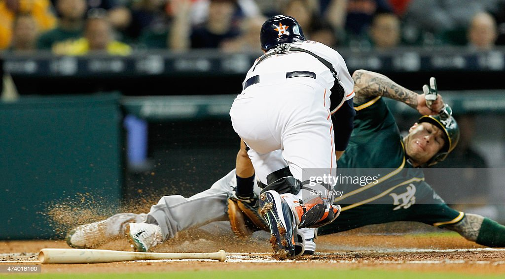 Brett Lawrie #15 of the Oakland Athletics is tagged out by Jason Castro #15 of the Houston Astros trying to score in the second inning at Minute Maid Park on May 19, 2015 in Houston, Texas.