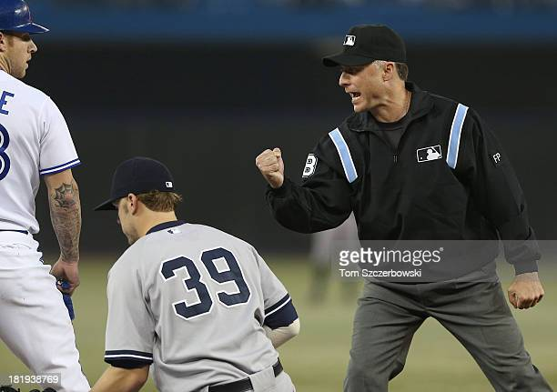 Brett Lawrie of the Toronto Blue Jays argues a double play call in the first inning as third base umpire Dan Iassogna makes his case during MLB game...
