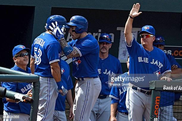 Brett Lawrie of the Toronto Blue Jays celebrates with teammate Melky Cabrera after hitting a home run against the Baltimore Orioles in the sixth...