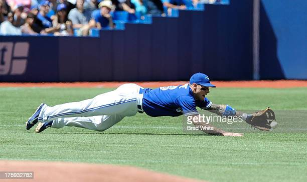 Brett Lawrie of the Toronto Blue Jays dives for the ball in the first inning during MLB game action against the Oakland Athletics August 10 2013 at...