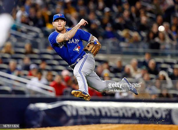Brett Lawrie of the Toronto Blue Jays throws to first base in the seventh inning attempting an out against Ben Francisco of the New York Yankees at...